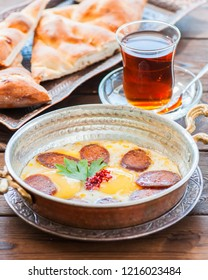 Turkish breakfast  - fried eggs with sausages (sucuk) and spices in a pan, glass of tea on a wooden background.