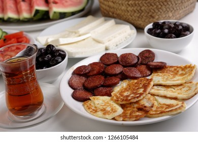 Turkish breakfast with haloumi cheese, roasted sucuk, fruits, and  Turkish tea