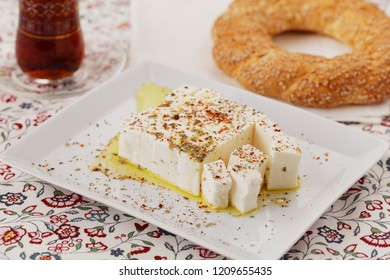 Turkish breakfast with sliced Feta cheese, Turkish bagel simit, and traditional Turkish tea