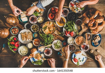 Turkish breakfast table. Flat-lay of peoples hands taking pastries, vegetables, greens, olives, cheeses, fried eggs, spices, jams, honey, tea in copper pot and tulip glasses. Middle Eastern meal