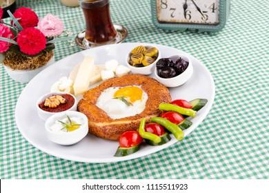 Turkish breakfast, tea and bagel on green table - kahvalti tabagi, simit, cay