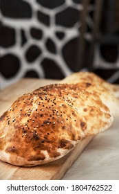 Turkish bun, tombik for making a traditional duner (Tombik Doner), oriental fast food. Tombic with sesame and caraway seeds. Fresh baked buns cool on table. Close-up, copy space, traditional cuisine
