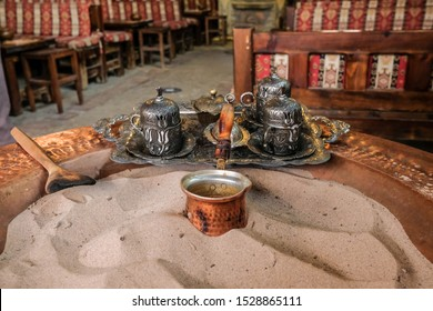 Turkish coffee brewing process in the sand and elderflower syrup, Sirince, İzmir, Turkey.