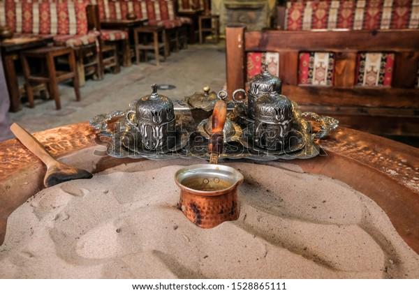 Turkish coffee brewing process in the sand and elderflower syrup, Sirince, İzmir, Turkey.