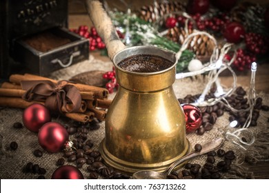 Turkish coffee in copper coffee pot on wooden background.