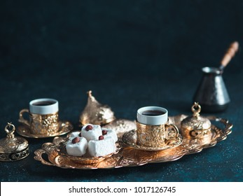 Turkish coffee with delight and traditional copper serving set on dark background. Assorted traditional turkish dilight or lokum and turkish coffee in metal traditional cups.Copy space.Selective focus