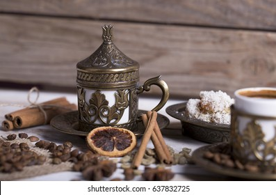 Turkish coffee with delight and traditional copper serving set on wooden