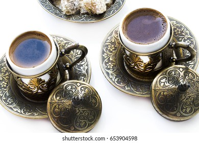 Turkish coffee with delight and traditional copper serving set on white background