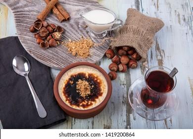 Turkish Cuisine dessert varieties. Baked rice pudding turkish milk dessert sutlac in earthenware casserole with hazelnuts.