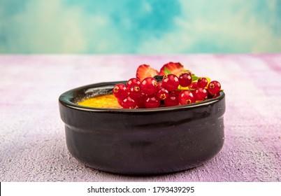 Turkish Cuisine dessert varieties. Muhallebi / Homemade Pudding. Baked rice pudding turkish milk dessert sutlac in earthenware casserole with forest fruits, berries, blackberries.