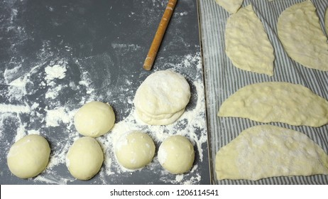 Turkish cuisine, dough balls, rolling pin and uncooked gozleme ready to cook.