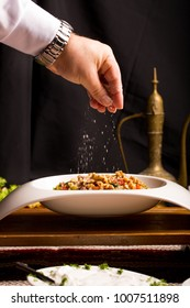Turkish cuisine eggplant salad with walnuts in white bowl on wooden tray in oriental ethnic style arrangement. Sesoning sprinkled by male chef hand. copy space vertical