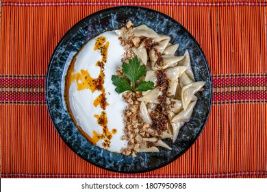 Turkish cuisine, Samsun style ravioli. Turkish ravioli manti preparation with meat, yoghurt, butter and red pepper. Manti concept, Anatolian foods on the table.
