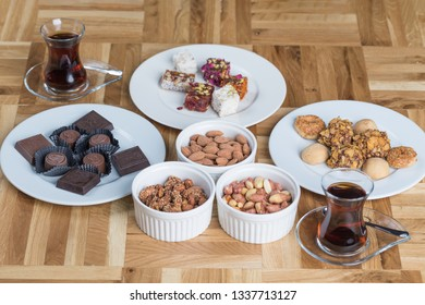Turkish delight with chocolate, nuts, cookies and traditional tea on a wooden table