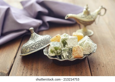 Turkish delight with nuts on metal oriental dish on wooden background