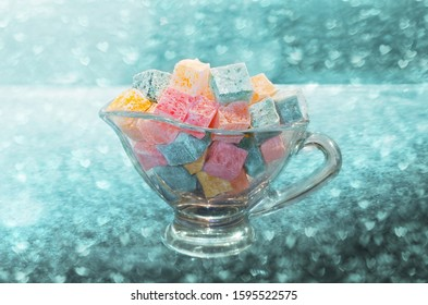 Turkish delight small colorful cubes in a glass bowl, on the background of bokeh hearts