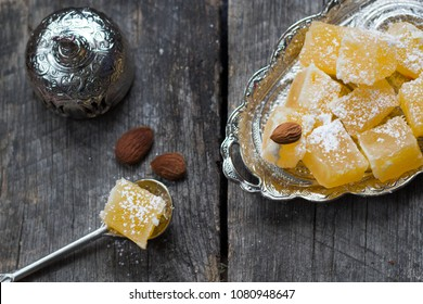 Turkish delight - tasty orange lokum, almonds and turkish coffee on wooden background