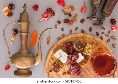 Turkish delight with tea and jug on a grey background with dry flowers