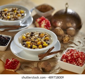Turkish dessert Ashura, Noah's pudding, with pomegranate seeds and walnuts (selective focus)