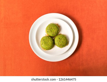 Turkish dessert kadayif with pistacchio on it. Also known antep kadayif in plate on orange background from top view