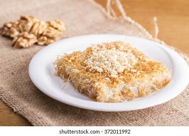 Turkish dessert kadayif with walnut on burlap texture
