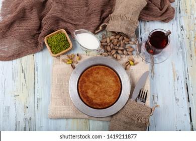 Turkish dessert kunefe, kunafa, kadayif with pistachio powder and cheese, served hot, very sweet. Turkish traditional dessert.