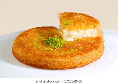 Turkish dessert kunefe, kunafa, kadayif with pistachio, walnut powder and cheese hot eaten a sweet