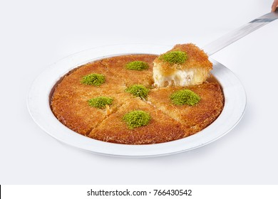Turkish dessert kunefe, kunafa, kadayif with pistachio powder and cheese hot eaten a sweet