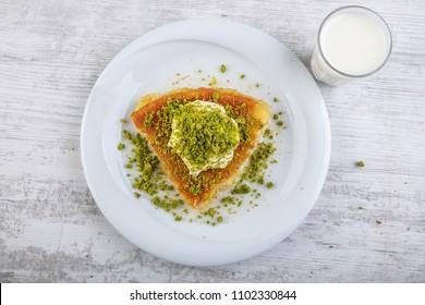 turkish dessert kunefe on kaymak, cream slide with pistachio powder