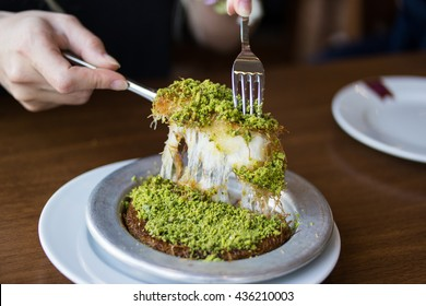 Turkish dessert kunefe with pistachio powder in silverl plate at restaurant