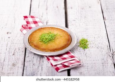 Turkish dessert kunefe with pistachio powder on white wood background