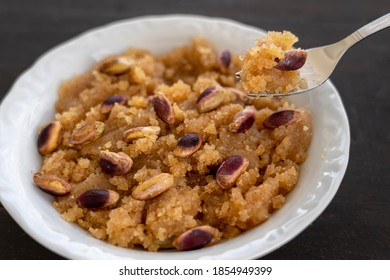 Turkish dessert; Semolina Helva with pistachio on wooden background