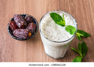 Turkish Drink Ayran or Kefir with fresh herbs in a glass with a bowl dry dates. Buttermilk made with yogurt. (yogurt, youghurt, kefir, ayran, lassi)