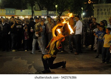 Turkish fire eater performing during the Ramadan while crowd  watching them bewilderedly,  Istanbul, 04 /10 / 2006
