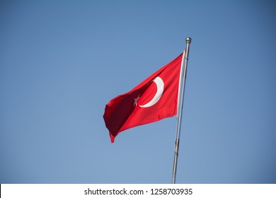 Turkish flag with red and white moon, blue sky