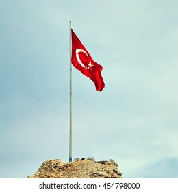 Turkish flag at the top of a fortress on a sky background