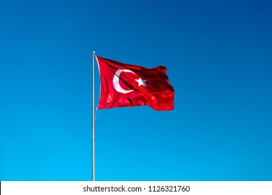 Turkish flag waving in blue sky.