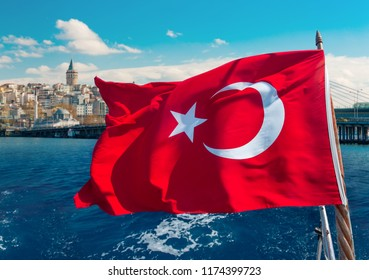 Turkish flag waving on a boat and Galata Tower on the background in Istanbul