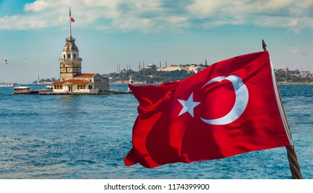 Turkish flag waving on a boat and Maiden'sTower and Topkapi Palace on the background in Istanbul