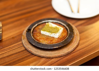 Turkish Foods ; Delicious traditional Turkish dessert, Kunefe with pistachio and cream. (Turkish dessert kunefe, kunafa, kadayif with pistachio powder and cheese hot eaten a sweet)