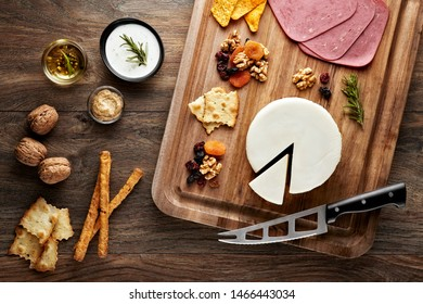 Turkish fresh kashkaval cheese on wooden table with wooden cutting board, knife and props. Overhead view.