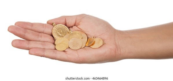 Turkish gold coin on female hand isolated on white background.