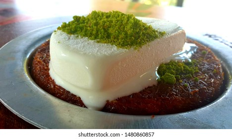 Turkish Ice Cream with Pistachio on the Kunafeh / Kunafa / Knafeh that is a middle Eastern dessert made with thin noodle-Like pastry