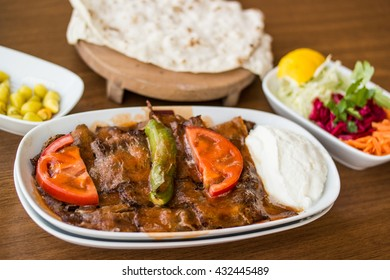 turkish iskender kebab with lavash on a wooden surface at restaurant