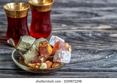 Turkish joys with different nuts are a glass of tea and a spoon. Eastern sweets. Traditional Turkish delight (Rahat lokum) on a wooden background. Side view.