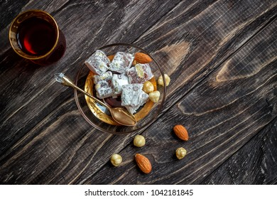 Turkish joys with different nuts is a glass of tea and a spoon. Eastern sweets. Traditional Turkish delight (Rahat lokum) on a wooden background. View from above .