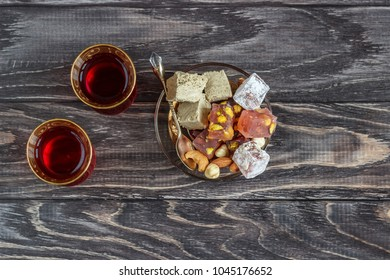 Turkish joys with different nuts is a glass of tea and a spoon. Eastern sweets. Traditional Turkish delight (Rahat lokum) on a wooden background. View from above