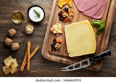 Turkish Kars Aged cheese on wooden table with wooden cutting board, knife and props. Overhead view.