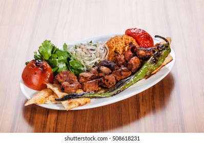 Turkish kebab served with yoghurt and vegetables on wooden table
