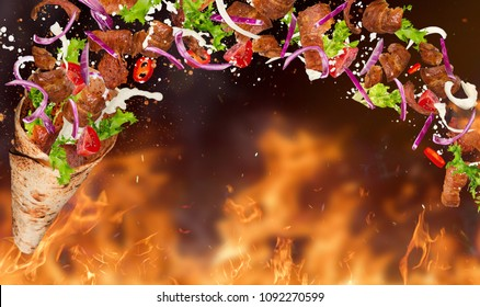Turkish Kebab yufka with flying ingredients and flames. Freeze motion.